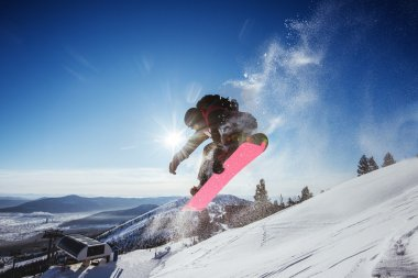 Snowboarder jumps on mountains