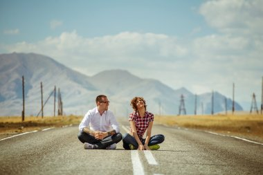 Couple sits on road