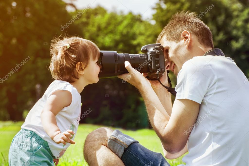 Happy father making photo of daughter
