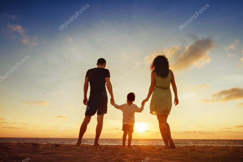 Family standing on sunset