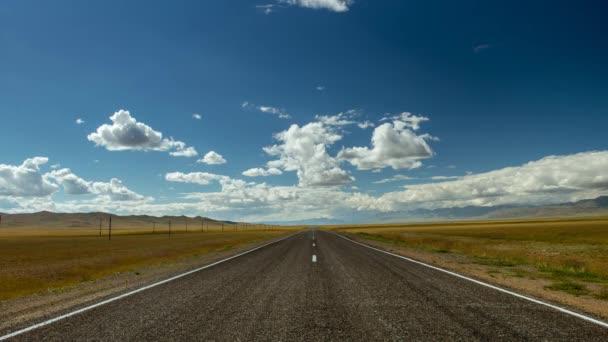 Zatažené oblohy a hory s silniční