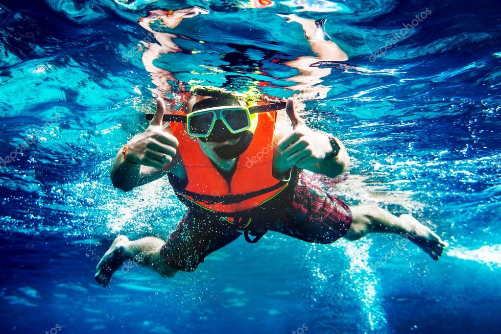 Man swims underwater and shows cool gesture