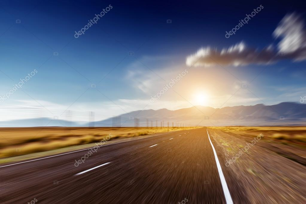 Straight road goes to mountains and horizon