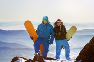 Two snowboarders stands on the top of mountain