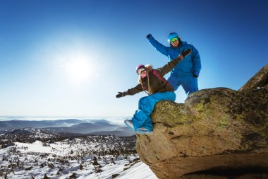 Happy couple of snowboarders having fun on the top of winter mountain stock vector