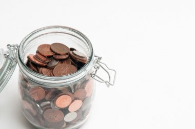 Coins in a glass jar for savings concept