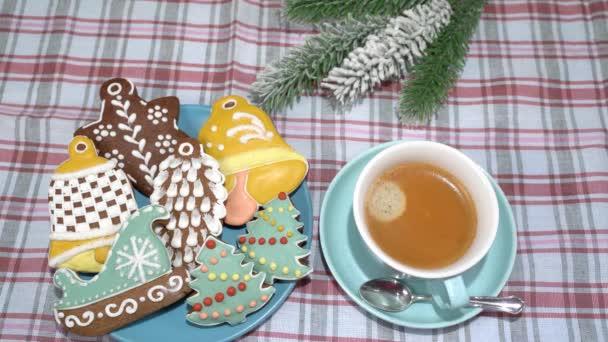 Egy tányér karácsonyi sütemények különböző formájú - hópelyhek, karácsonyfák, kesztyűk, csillagok, szánkó, kúp, harangok és egy csésze kávé az asztalon.