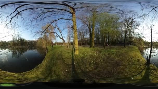 Muž v Green parku je Walking stromy sférické Panorama Video jezero řeky v lesních holé větve slunečné jarní den Blue Sky malé planety Video