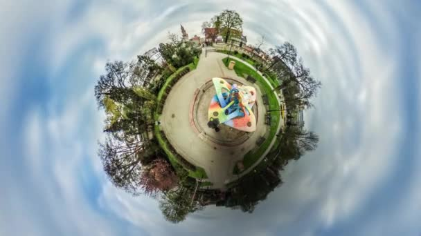 People Walk by Footpath Park Alley Video 360 vr Panoramic View of Square Sculpture is Located in the Middle of the Park Green Lawns Trees Opole Poland