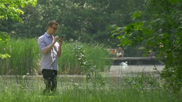 Man Clicks a Mobile Phone in Green Park Lake Bank Man in Glasses is Holding a Smartphone Flying Poplar Cotton Swan on a Lake Fresh Green Trees Sunny Summer