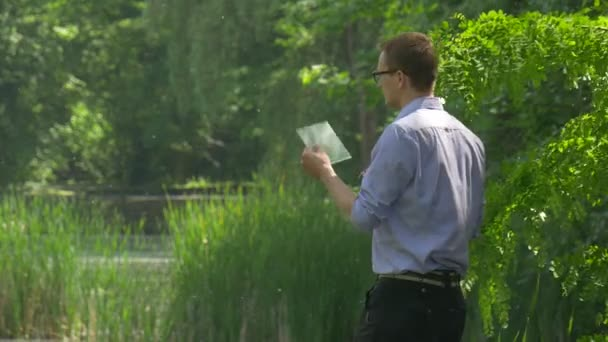 Man Standing Holding Virtual Tablet in Green Park Forex Internet Shopping Chat Businessman Spends Time at the Nature Fresh Green Trees Sunny Summer Day