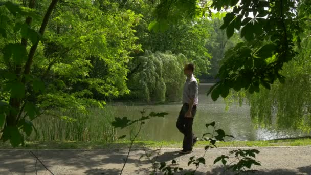 Man Walking With Tablet in Park Alley Along River Holding a Virtual Tablet Spend Time at the Nature Near Lake River Fresh Green Trees Sunny Summer Day