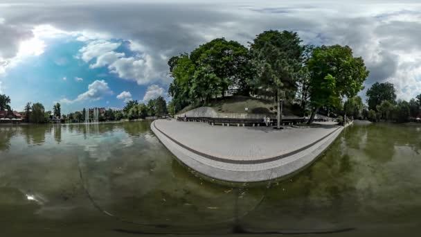Video muž 360vr poblíž rodinné dvojice vody rybníka městský den Opole Park a Kid chůzi dlažební kameny slunce odraz ve vodě zelené stromy léto