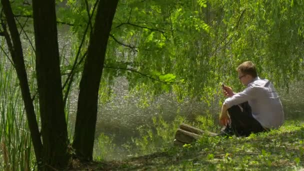 Man With Mobile Phone Sits to a Ground Lake Bank in Park Typing a Message Number Spend Time at the Nature Under Fresh Green Trees Willow Sunny Summer Day