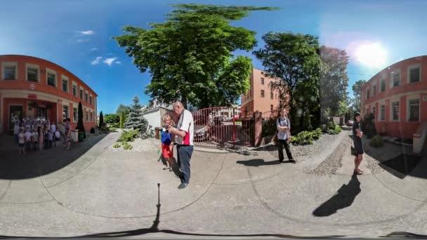 360vr videóinak ünnepe az utolsó nap Opole boldog gyerekek iskolai tanár pedig napsütéses nyári nap közelében iskola bejárat kék égbolt zöld fák az udvari