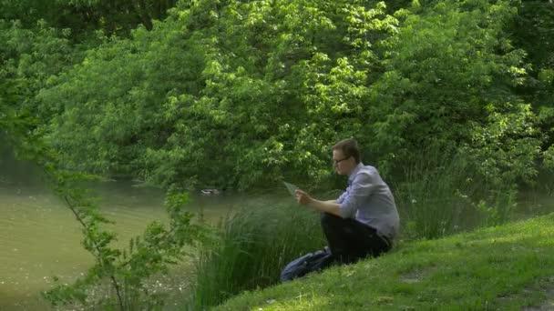 Üzletember, mobil telefon zöld dombon ülő gazdaság egy Smartphone tölti idejét a Park friss, zöld fű-fa napsütéses nyári napon
