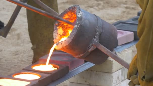 employees of a foundry helps to pour out metal from a small metal
