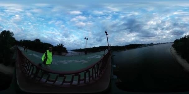 360vr Video člověka je natáčení mostu podél plotu město den Kyjev turista v citronově žluté sako lidé jsou procházky venku soumraku krajina řeky banky zataženo