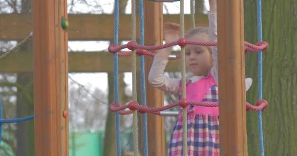 Kleines Mädchen klettert langsam auf Strickleiter nach oben