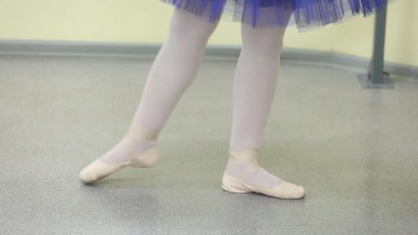 Close-up of a ballerina as she performs exercises on a dark stage or in the studio. Womans legs in pointe shoes. The ballerina shows the classical ballet steps. Slow motion