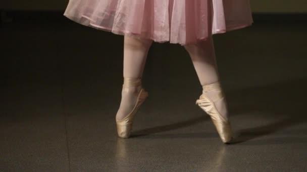 Großaufnahme einer Ballerina, die auf einer dunklen Bühne oder im Studio Übungen macht. Frauenbeine in Spitzenschuhen. Die Ballerina zeigt die klassischen Ballettschritte. Zeitlupe