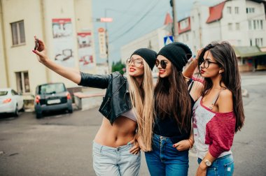Three beautiful girls making selfie