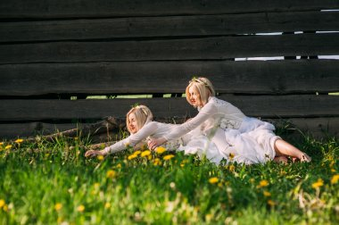 Twin sisters sitting at a wooden wall