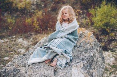 girl covered in blanket in park