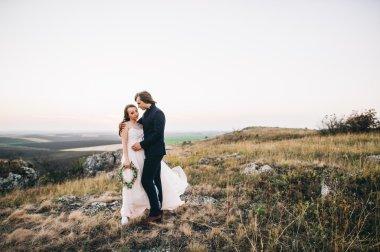 beautiful stylish groom holding fabulous bride