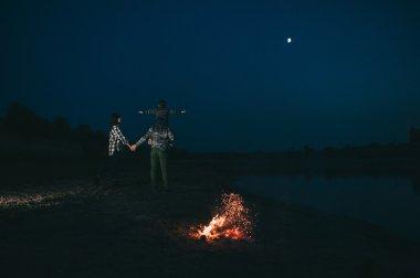 Happy young family near campfire