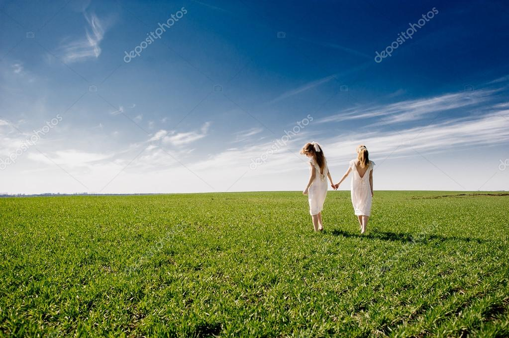 two twin blond sisters on lawn