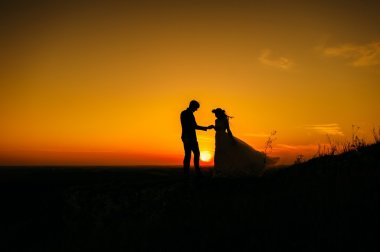 silhouettes of couple at sunset
