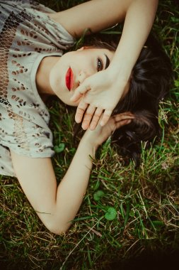Brunette girl lying on the dry grass