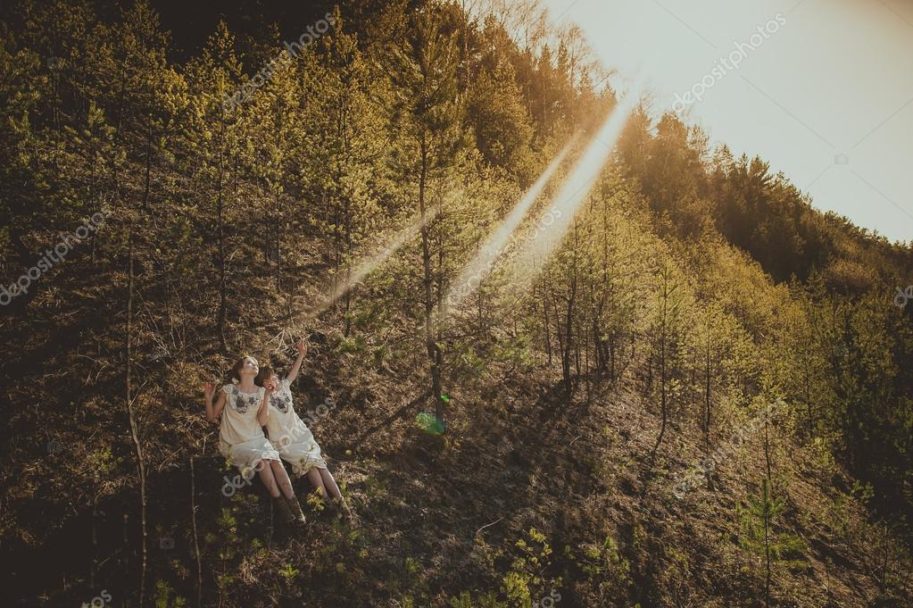 two twin blond sisters in forest