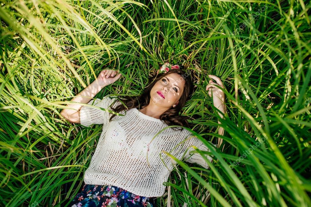 girl lies in green grass