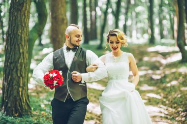 bride and groom walking in the forest