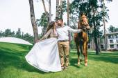 Fotografie  couple standing next to a horse