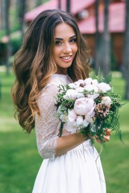 bride with white bouquet in park