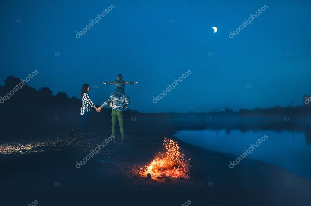 Happy young family and campfire