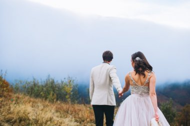 Newlyweds on a walk in mountains