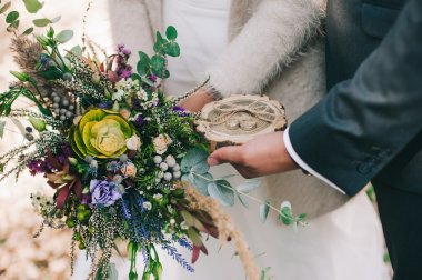 Groom holding wedding rings