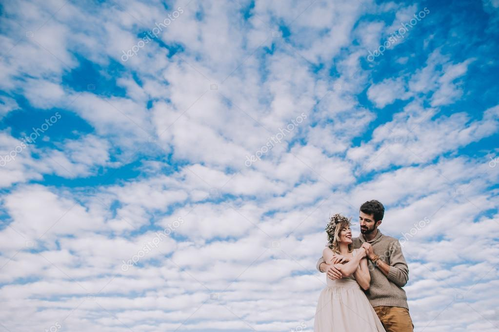 Couple holding hands against the sky