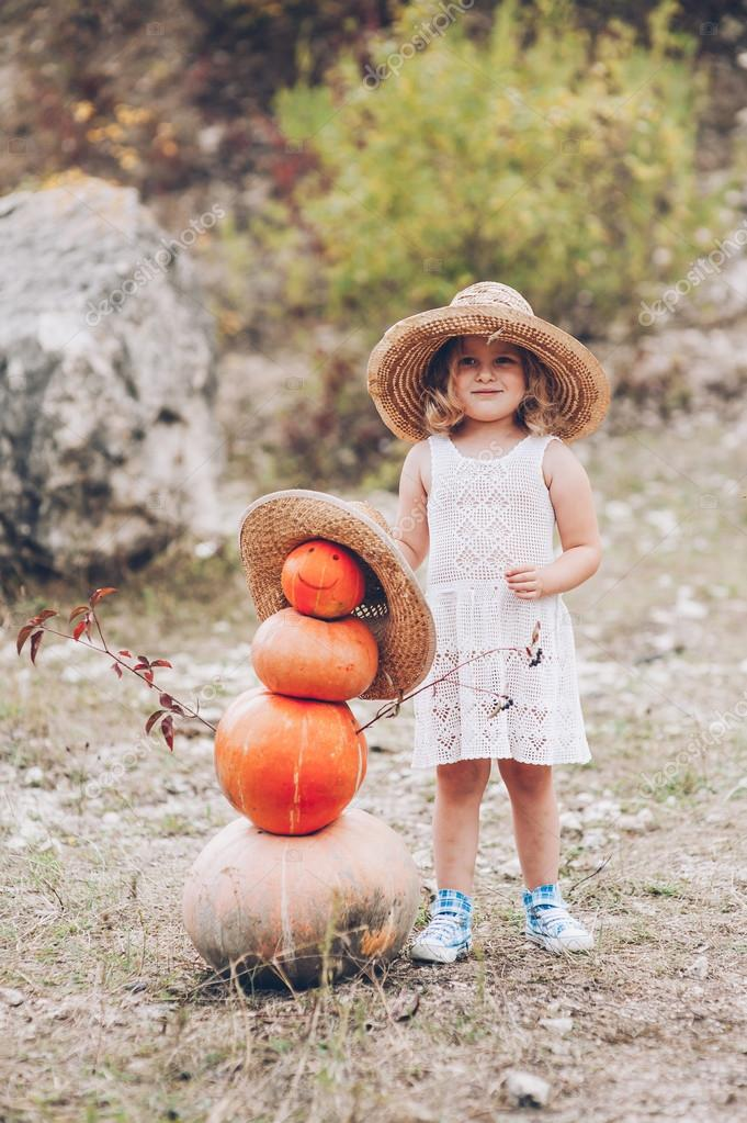 Little girl in a straw hat by pumpkins