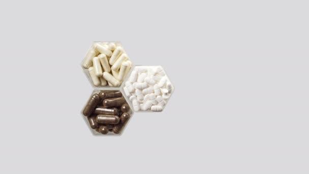 Verschiedene Pillen und Kapseln in sechseckigen Gläsern erscheinen auf grauem Hintergrund