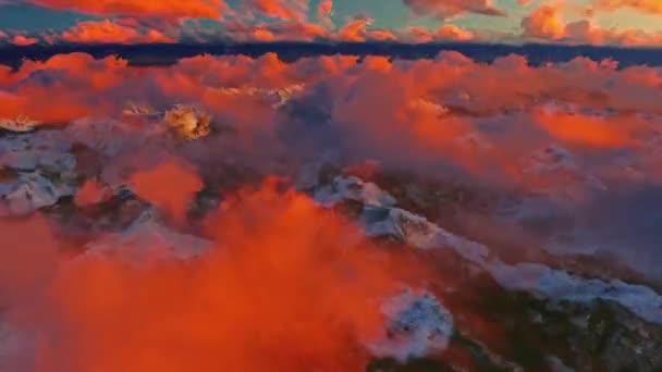Fotoaparátu letí nad mraky nad horami na pozadí při západu slunce