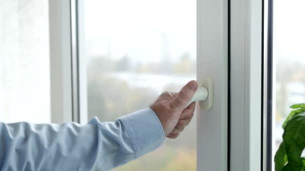 Ruka muže otevírajícího velké okno z kanceláře