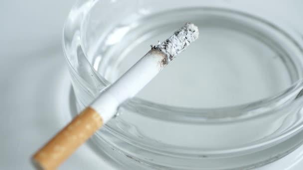 Nahaufnahmen mit einer Zigarette, die im Aschenbecher raucht