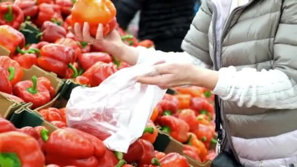 Woman buying red sweet peppers at the market