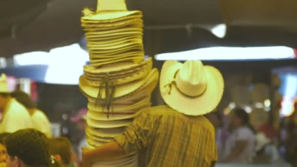 3f670743f11f67 SAN MIGUEL DE ALLEGED, MEXICO - CIRCA MAY 2015 - Man carrying many cowboy  hats in a busy market in Mexico– stock footage