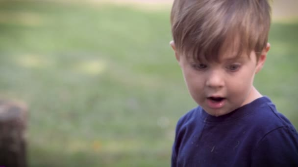 Slow mo of a child dropping his toy and looking up to his dad for approval